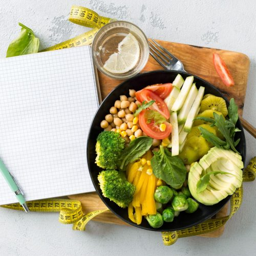 Vegan healthy balanced diet concept. Vegetarian buddha bowl with blank notebook and measuring tape. hickpeas, broccoli, pepper, tomato, spinach, arugula and avocado in plate on white background. Top view