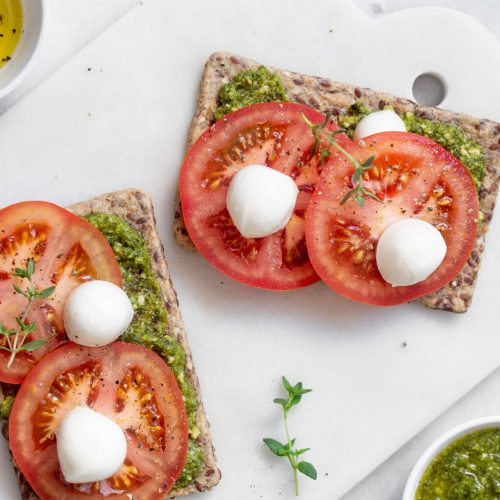 Mozzarella cheese, tomatoes and  pesto bruschetta on light marble background, top view. Pesto and sandwiches